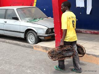 Vendeur de viandes séchées passant devant la maison communale de Kimbanseke  à Kinshasa. Photo Don John Bompengo/ juin 2013