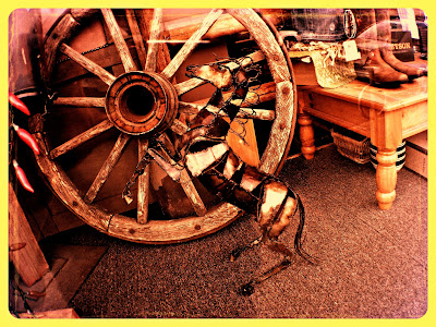 Front window display of an old wagon wheel and a brass horse in downtown Renton, Washington.