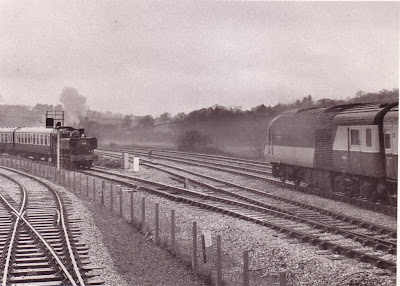 "The press special hauled by 1638 ""Dartington"" waits for the road out on to the mainline from Totnes Riverside as an Inter-City 125 pulls away from Totnes station - 14th April, 1985.  Photo:  Roger W. Penny"
