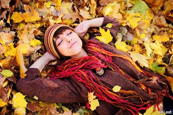 ảnh cô gái nằm dưới lớp lá rơi rụng của mùa thu