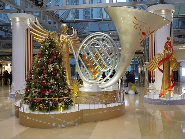 large angel playing a large French Horn next to a Christmas tree