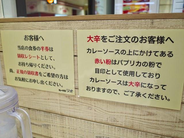 店内に書かれた食券レシートと、大辛カレーのパプリカの案内