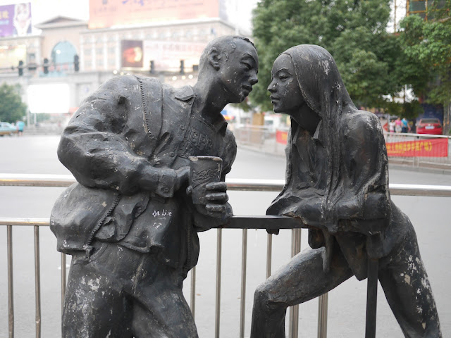 "statue of a male holding a Coca Cola glass ""speaking"" with a statue of a female"