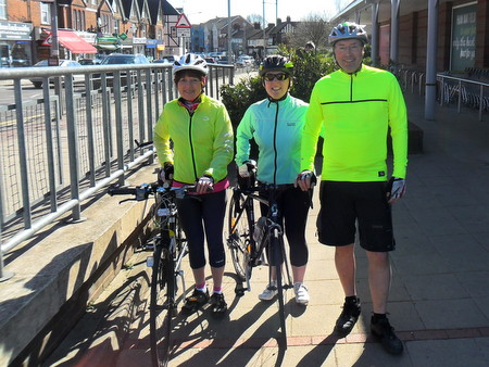 Three cyclists standing by their bikes