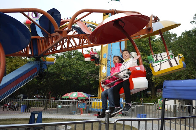 Two children on parachute amusement park ride in Zhuhai, China