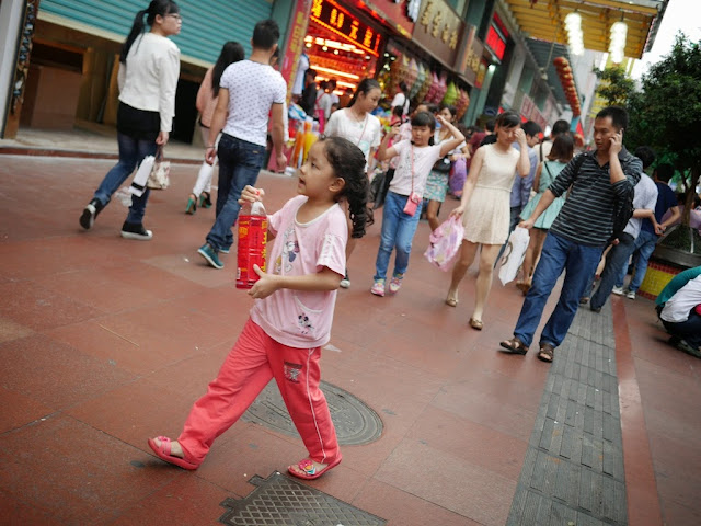 girl carrying a large bottle of Wang Lao Ji.