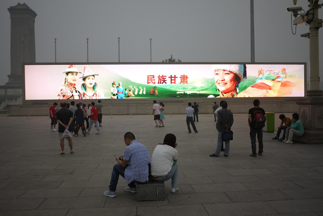 people in front of a large video display at Tiananmen Square