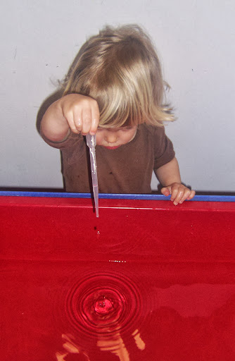Child uses a pipette to make drops of water.