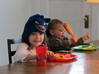 Kids at the table.  Bean is waving a corn dog and yelling.