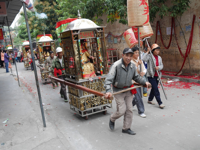 man pulling one of the gods for a Gods Parade in Maoming, China