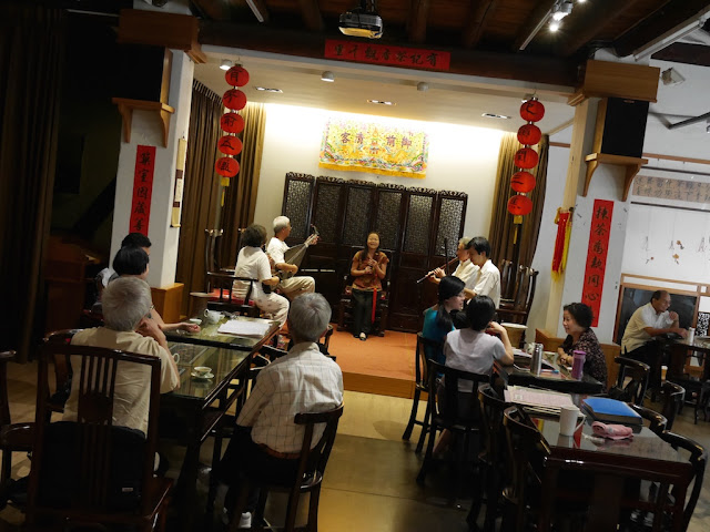 people drinking tea in front of a live traditional Chinese music performance