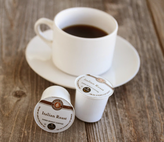 photo of two k-cups with a cup of coffee in the background