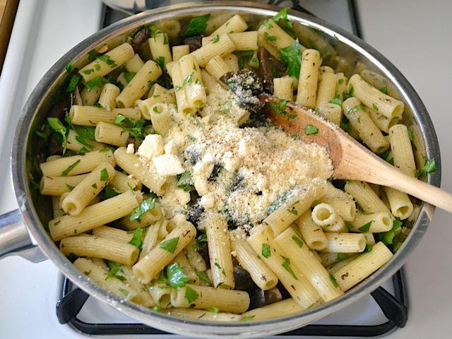 parmesan cheese added to top of pasta dish in skillet