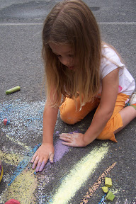 Child exploring what happens to wet chalk on blacktop.