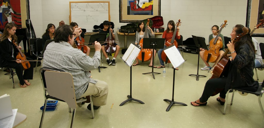 Eight young people sitting in a circle playing viol. Roland sits and conducts, while Annette plays along.