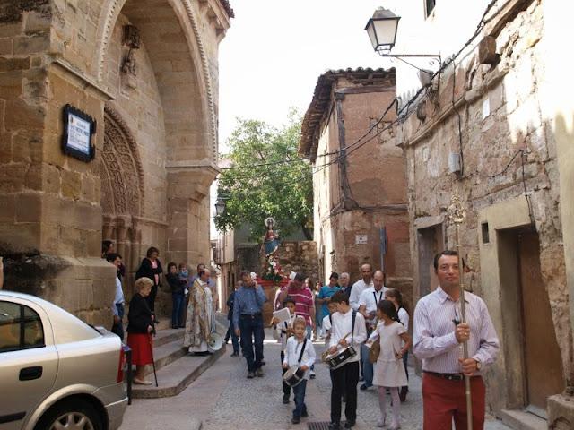 La procesión saliendo de la parroquia de San Vicente, precedida por el Hermano Mayor con la insignia y los miembros de la banda de música