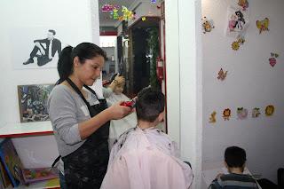 La peluquera trabajando con un niño junto al espacio para los pequeños