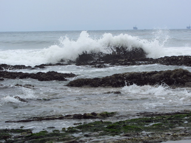 wave splashing on rocks as it rolls in