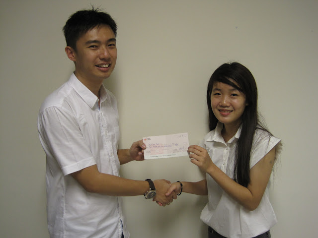 Tenna Ong Li Sian (right) receiving the Bursary Award from Mr Lim Kian Kiat, Treasurer of AJCAA.