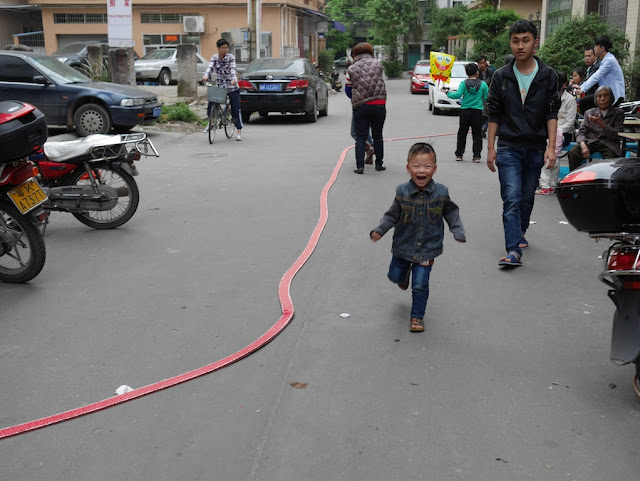 boy excitedly running by a long strip of firecrackers in Maoming, China