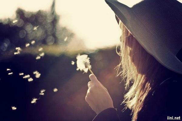 ảnh cô gái đang thổi những cánh hoa
