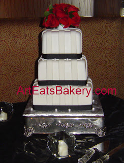 White fondant striped three tier custom wedding cake with black ribbons, sugar pearls and fresh red roses topper