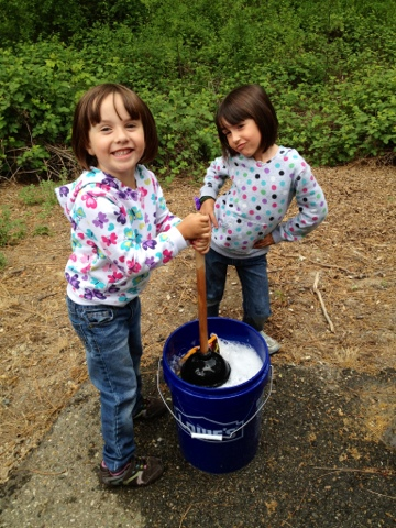 Kids handwashing diaper laundry while camping