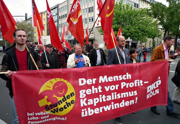 Demonstranten mit DKP-Fahnen und Transparent: »Der Mensch geht vor Profit – Kapitalismus überwinden! DKP Köln«.