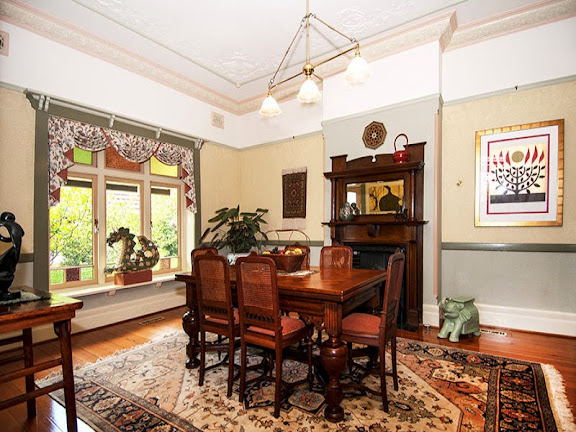 A bay window, ornate ceiling and cornices, picture rails, wooden fireplace are perfecty Federation style. Also the coloured glass panels.  The dining furniture is however not of Federation style, since it is a complicated style of an earlier era.