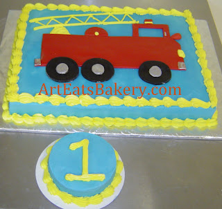 Blue and yellow butter cream boy's 1st birthday cake with red fire truck and smash cake