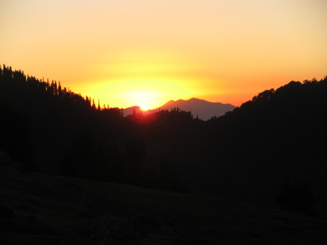 orange sun falling below the hills