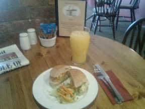 glass of orange juice next to salad roll on hardwood cafe table, newspaper and condiments