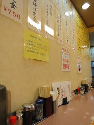 店内のカウンター席。壁には定食のメニューがペタペタ貼ってある。