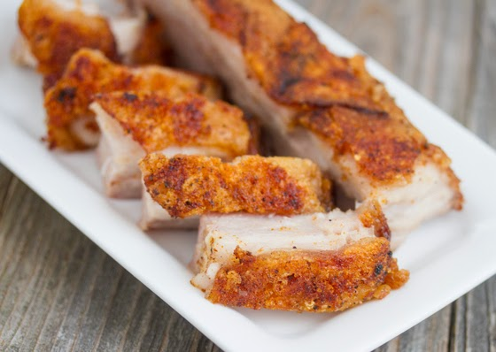a close-up of sliced crispy pork belly on a white serving plate