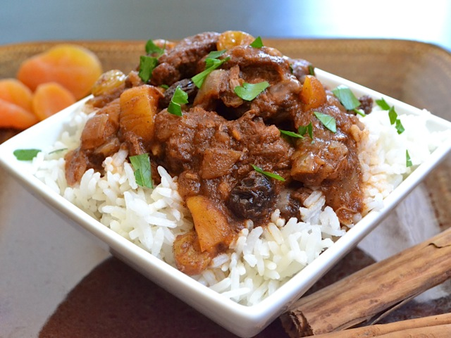 moroccan beef stew on a bed of white rice plated on a white square plate