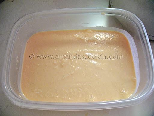 A plastic container of orange ice cream.