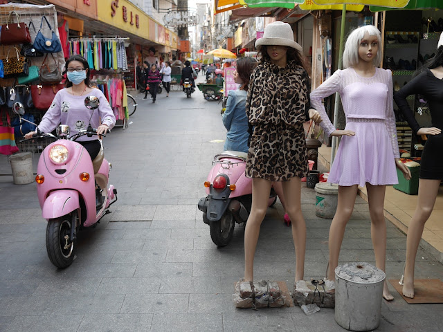 young woman wearing a face mask riding a pink motorbike past mannequins in Yangjiang, China