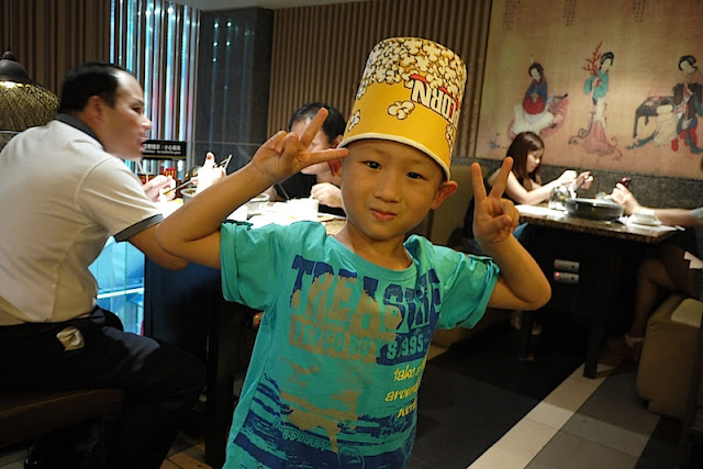 boy wearing a paper popcorn bucket as a hat in Shenzhen, China