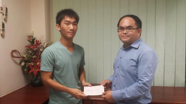 Glenn Zeng Zhaosong (left) receiving the Bursary Award from Mr Kent Teo, President of AJCAA.