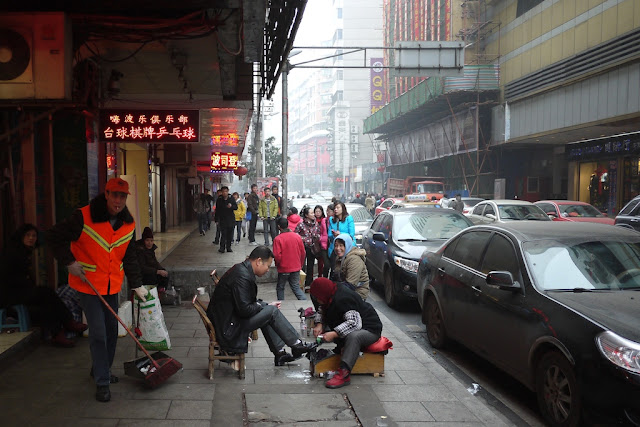 shoe shining on a sidewalk in Hengyang