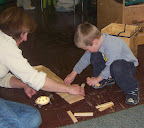 Child and teacher building together to make a structure for a toy turtle.