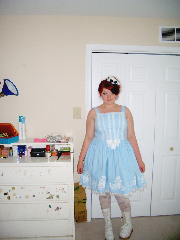 A fat, young, pale-skinned woman in a blue Lolita-style dress stands next to a white dresser covered in stickers.
