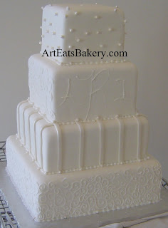 Four tier custom unique white fondant wedding cake with royal icing curlicues, pearls, stripes and monogram design