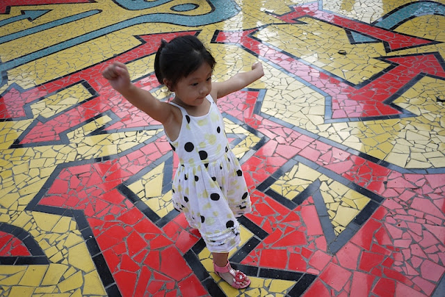 little girl on tiled ground covered with numerous arrows