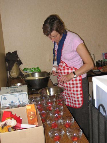 Christa is ondanks de beperkte bewegingsvrijheid toch niet tegen te houden en schept dapper aardbeien in de dessert glazen.