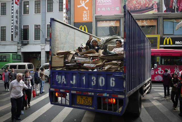 two men lying on cardboard on the back of a truck in Guangzhou, China