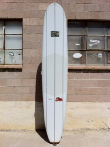 A 10'2 by 24 with a wood tail block and 3 ceder wood stringers. Glossed finish with a single fin set up.