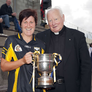 Dean Davies presents Ballycran Captain Naomi Morgan with the Down Senior Camogie Championship Cup