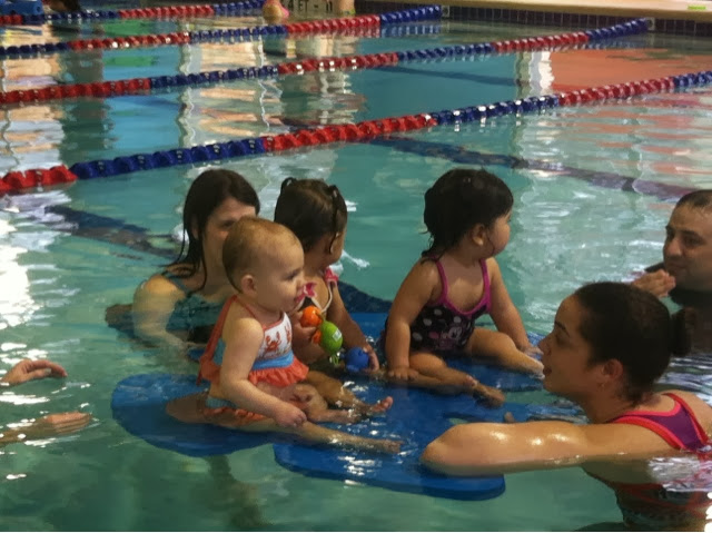 Babies enjoying the baby swim lessons in warm water on a float.