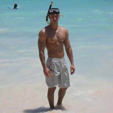 Hot guy with good pecs standing on a beach, ready to snorkle!